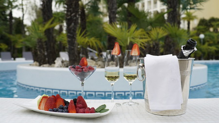comfort food: Still life photo of champangne and fruits in the pool background.