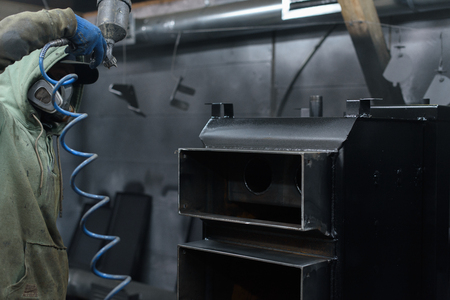 fuel chamber: Look from behind at man working on black solid fuel boiler