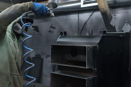 central chamber: Man sprays black paint on solid fuel boiler