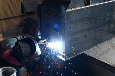 fuel chamber: Man solders holes in black solid fuel boiler