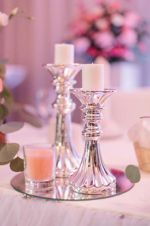 Kleine weiße Kerzen stehen auf hohen Silberhaltern Standard-Bild - 68603434