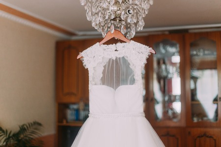 luster: Luxurious wedding dress hanging on luster at dressing room.