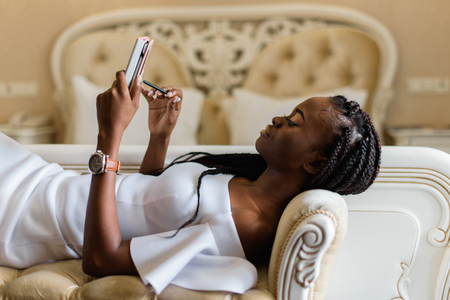 admiration: sexy african woman is on the sofa and chatting with friends using the tablet. Vip luxury hotel with amazing classic interior Stock Photo