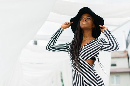 Portraite photo of adorable, charmed woman with black skin. Pretty girl smiling and take her hands on the hat. Stock Photo