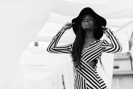 Black and white portraite photo of adorable, charmed woman with black skin. Pretty girl smiling and take her hands on the hat.