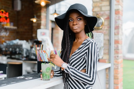 Attractive black girl in bar with cocktail in her hands. Many straws for cocktails on the bar. Ice cocktails. Mohito.