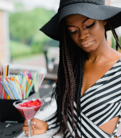 Adorable, charmed black girl in bar with red cocktail in her hands. Many straws for cocktails on the bar. Ice cocktails. Margarita. Stock Photo