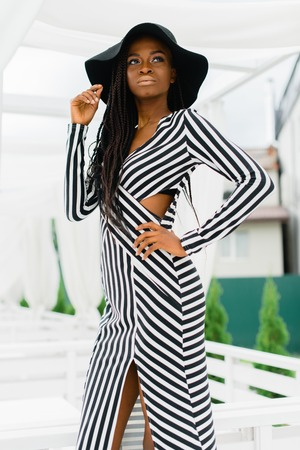 Photo of adorable, charmed woman with black skin. Pretty girl smiling and take one hand on the hat, another one to her waist. Stock Photo