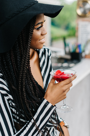 attractive adorable african woman in bar with cocktail Margarita in her hand, drinking and smiling. Ice cocktails. Margarita.
