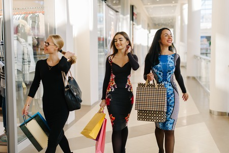 Three charmed attractive women have shopping in big mall. Female wearing dresses with lond sleeves and have shopping bags in their hands. They are very happy and playing with hair.