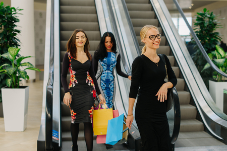 second floor: Three friends have shopping in mall. They using escalator to go down from the second floor. Girls wearing long dresses and shopping bags in their hands. Blonde girl has a ponytail and glasses.