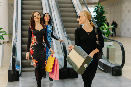 second floor: Three friends have shopping in mall. They using escalator to go down from the second floor. Girls wearing long dresses and shopping bags in their hands, playing with it. Blonde girl has a ponytail and glasses. Stock Photo