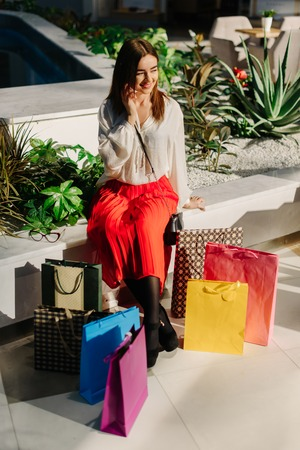 Pretty charmed woman on bench in big mall talking by phone with friends after shopping. Attractive woman wearing midi red skirt, white shirt, and high heels. Many shopping bags are near. Female has happy talk.