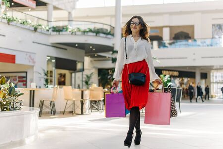 Pretty brunette girl in mall after shopping. Attractive woman wearing midi red skirt, white shirt, glasses and high heels. She has shopping bags in her hands. Walking in mall, smiling and looking at somebody. Her hair fluttering