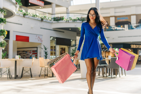 Charmed woman in short blue dress with long sleeves on high black heels and glasses after shopping. Girl has many colorful shopping bags in her hands. Mall decorated with green trees