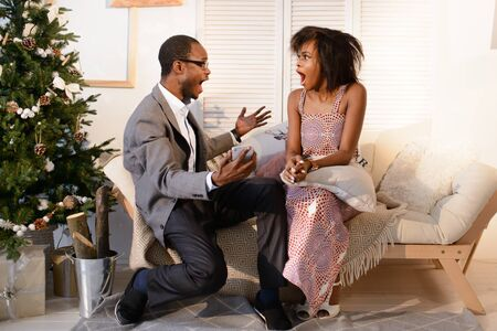 cant: The handsome attractive afro-american man is making a great surprise to his girlfriend on the Christmas eve, she is very surprised and cant deal with emotions Stock Photo