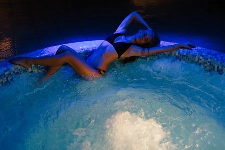 Beautiful young Sexy woman lying down on edge of Jacuzzi 版權商用圖片 - 69867595