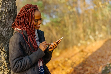 Pretty woman standing near tree in the autumn park at sunset. Girl chatting in internet using her phone and smiling. Beautiful autamn park Stock Photo