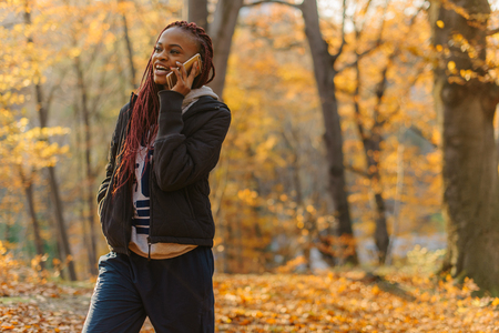 Cute african american girl walking in autumn park and has a conversation. Woman have a rest on fresh air.