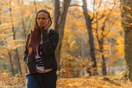 earing: Cute african girl walking in autumn park and talking by phone. Woman have a rest on fresh air. Stock Photo
