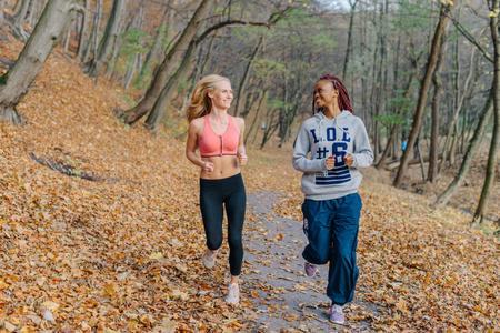 Glückliche Frauen, die in autamn Park laufen. Blonde und afrikanische Mädchen werden morgens trainiert