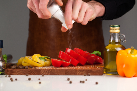 Male chef spicing sweet pepper with salt using salt-shaker. Vegetables placed on a wooden cutting board