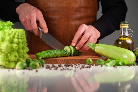 Chef slicing fresh cucumder on a wooden cutting board among vegetables and a bottle of oil