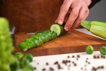 Sliced cucumber on a wooden cutting board neat set of different vegetables. Placed in front of chef Stock Photo