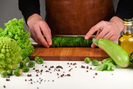 Chef holding sliced cucumber together on a wooden cutting board. Vegetables placed on a white surface and wooden board
