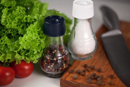 Closeup pepper an salt jars placed on a white surface with chefs knife, wooden cutting board and some vegetables