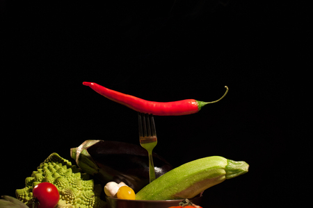 set of vegetables with top red chilly pepper on a black background
