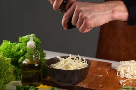 pepperbox: Set on vegetables. Chef dressing chopped cabbage with pepper. Dark bowl with cabbage inside Stock Photo