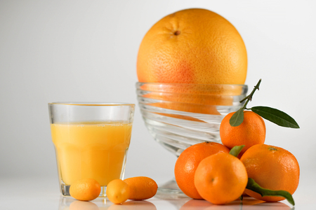glass of juise and ripe sweet tangerines with leaf, isolated on white background in front of big orange in a glass bowl