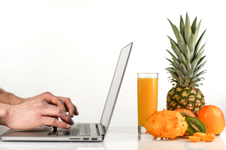 Person taping on a laptop computer near composition of tropical fruits on a white background