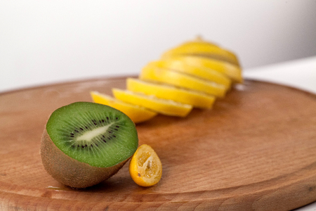 Sliced lemon and a half of kiwi on awooden cutting board Stock Photo