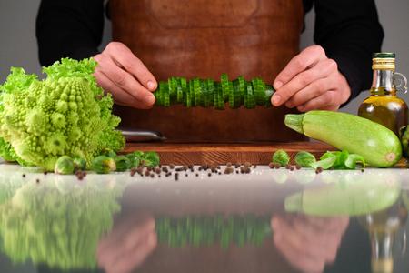 caloric: Close-up of mans hands holding sliced fresh cucumber above wooden brown cutting board. Set og green vegetables.
