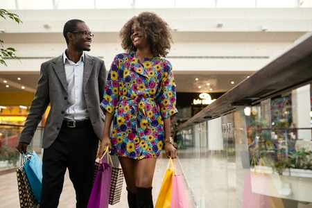 Smiled afro-american couple walking together in a shopping mall with a lot of coloured shopping bags Banque d'images
