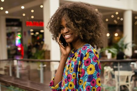 afroamerican: Afro-american woman talking on the phona and smiling, standing in a shopping mall