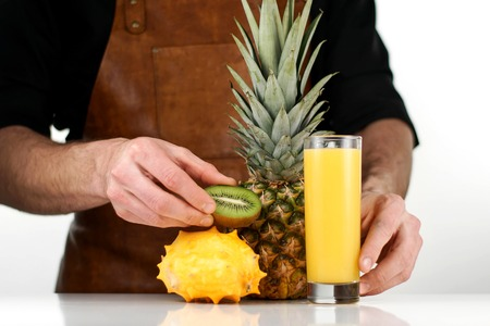 Chef making a composition of fresh ripe tropical fruits on a white table and white background Stock Photo
