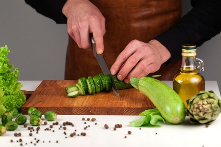 Chef cutting long green cucumber on a wooden cutting board among green vehetanles Stock Photo