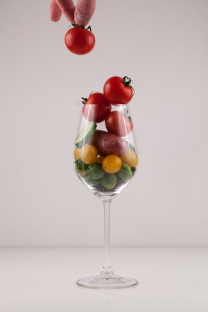 Hand holding small tomato above wineglass filled with vegetables Stock Photo