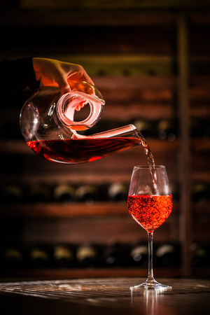 Wine pouring into a glass from figured carafe. Composition placed in a wine vault. Stock Photo