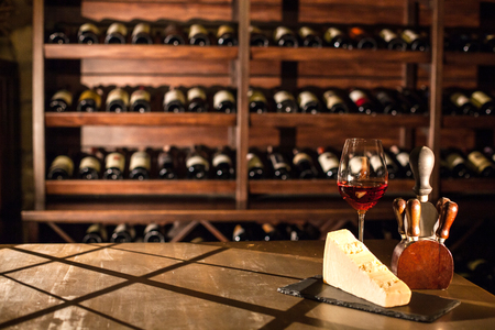 Composition in wine vault. Wine glass, cheese and accessories on a wooden table. Stock Photo