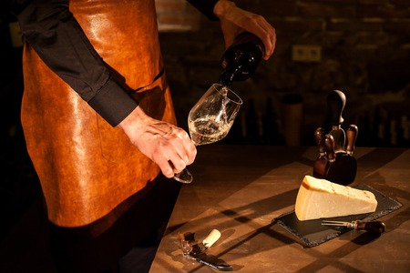 sommeliers: Sommeliers hands holding a bottle of wine and glass. Wine pouring into a glass. Wine vault location.