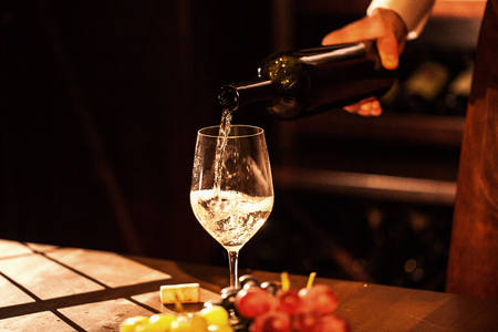 Hand holding a bottle of wine and pouring wine into a glass. Wine vault. Stock Photo
