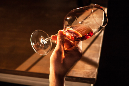 Close-up shot of glass of wine in a hand. Stock Photo