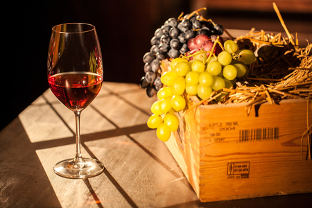 Wine glass and box with fruits placed on a wooden table in sunlight.