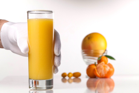 Close-up of hand in white gloves holding a glass of orange juice on a white surface