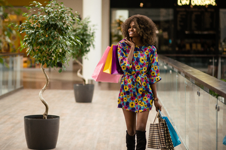 Beautifull, well-dressed afro-american girl walking after shopping in a shopping mall. Banque d'images