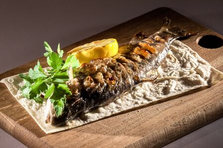 gilt head: Grilled fish with herbs and lemon placed on a pita bread. Food on a wooden board.